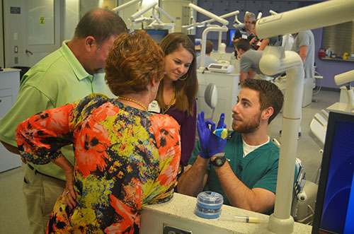 Third-year dental student Travis Moore provides a simulation lab demonstration for first-year Mary Bec Keith and her parents during the school's 4th  Annual Family Day Celebration.  Nearly 230 attendees enjoyed interactive sessions and a tailgate lunch.